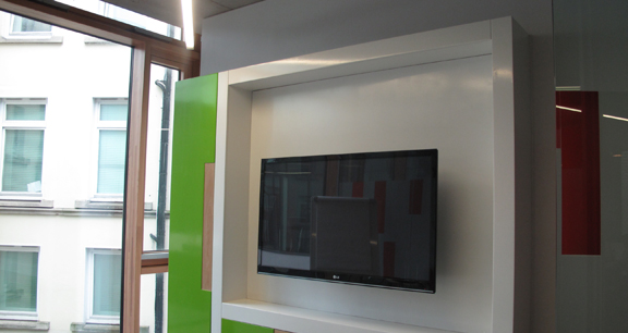 Image of wall mounted TV screen in conference room of office interior.